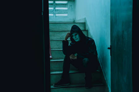 Portrait of white mask and hoodie sitting on old stairs. Selective focus on hands. Sadness, despair, dark, concept