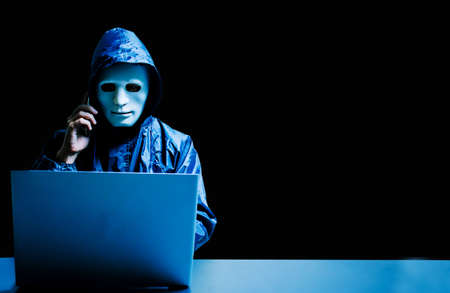 Anonymous computer hacker in white mask and hoodie. Obscured dark face using laptop computer for cyber attack and calling on cellphone, Data thief, internet attack, darknet and cyber security concept.