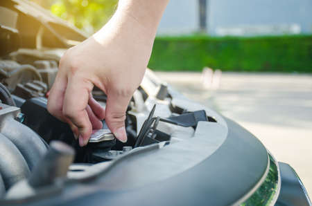 Man hand checking level of coolant car engine. Check and maintenance the coolant in car with yourself.