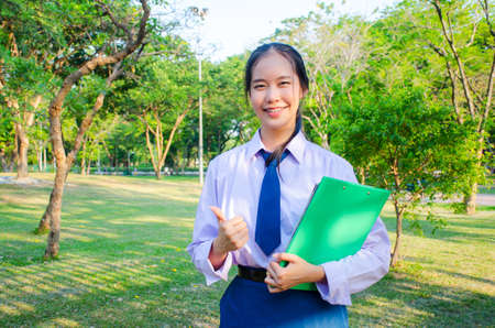 Portrait of thai high school student uniform teen beautiful girl happy and relax holds notebooks in his hands at the park, thumbs up.