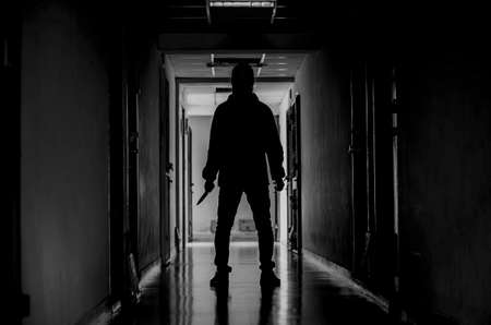Mord-, Tötungs- und Personenkonzept - Krimineller oder Mörder, der eine Maske in Silhouette trägt und Messer in einer Eigentumswohnung am Tatort hält Standard-Bild