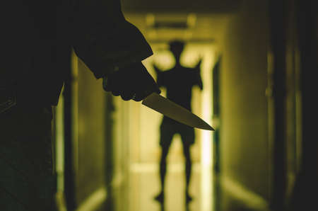 Close up of Hand with knife following young terrified man, Bandit is holding a knife in hand. Threat Concept