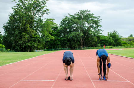 Training teammates. Two male athletes is warming-up,Two runners standing on the racetrack at the stadium stretching their legs before running Reklamní fotografie