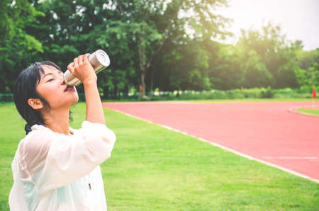Stunning fitness woman drinking water from bottle during running at the stadium in sunny morning. Empty space