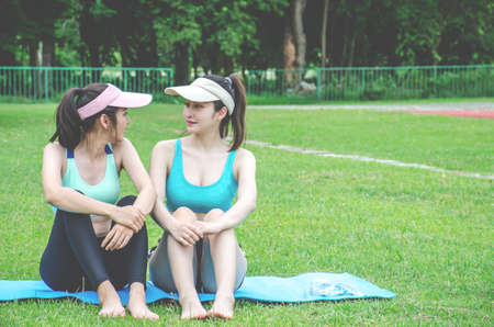 Portrait of cheerful young woman sitting on yoga mat and talking  while having break after training at stadium. Smiling sportswoman relaxing after workout with his friends at gym. Smiling girl having conversation