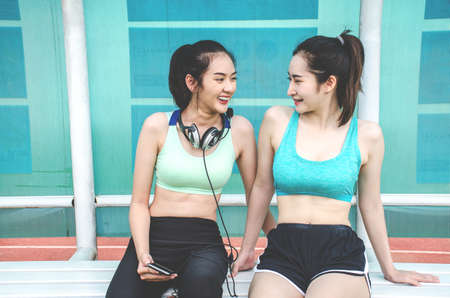 Young two sports women friends sitting at the park and relaxing after jogging outdoor.They talking and laughing.