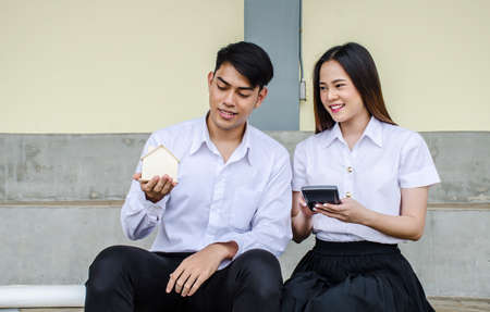 Portrait of young man and girl in university uniform sitting and hold a small house and calculator, Concept of sustaining a house between two people. Helping your partner in owning a house