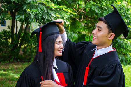 A man and woman couple dressed in black graduation gown or graduates with congratulations with graduation hats is standing, smiling and holding hat with the park background