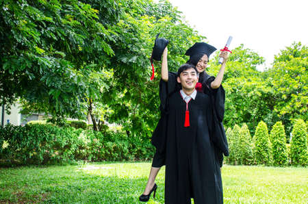 A man and woman couple dressed in black graduation gown or graduates with congratulations with graduation hats is standing, she is hugging him from the back is smiling and holding hat with the park background