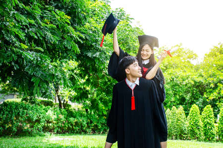 A man and woman couple dressed in black graduation gown or graduates with congratulations with graduation hats is standing, she is hugging him from the back is smiling and holding hat with the park