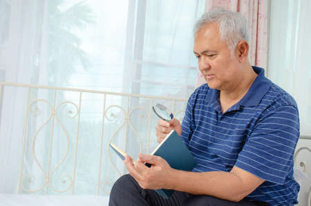 Portrait of senior man with a magnifying glass is reading a book while sitting on couch at home Фото со стока