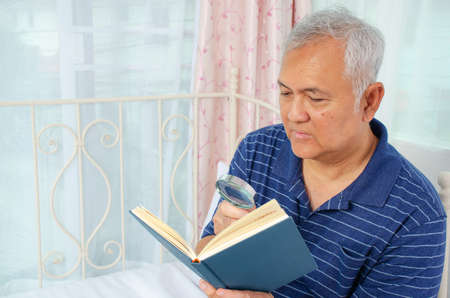 Portrait of senior man with a magnifying glass is reading a book while sitting on couch at home