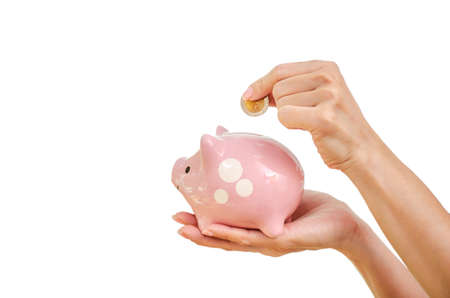 Woman hand putting money coin in to piggy for saving money wealth and financial concept, isolated on the white background