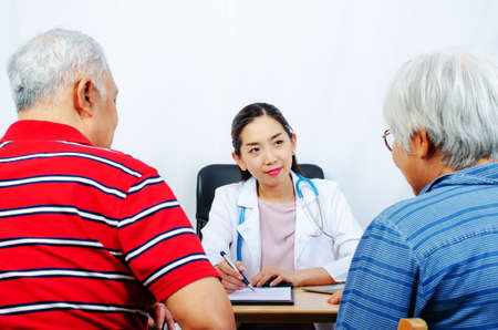 Couple senior patient visiting listen to young woman doctor in a hospital,Medicine and health care concept. Banco de Imagens