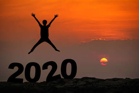 Silhouette of young man happy jumping and hand up between 2019 new year, sky and sun light background. copy space for text. Future and time passing concept.