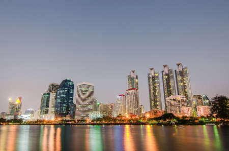 Cityscape image of Benjakitti Park at sunset time with reflection in Bangkok, Thailand, Cityscape image of Benchakiti Park, Night city, city of life 写真素材