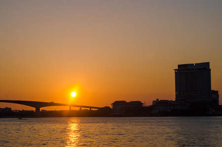 Silhouette of Bangkok Transportation at Sunset with Building along the river 写真素材