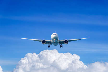 Passenger plane in flight. Aircraft fly high in the sky above the clouds. Front view of airplane.