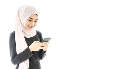 Portrait of beautiful asian muslim woman in a black hijab smiling and using mobile phone isolated over white background
