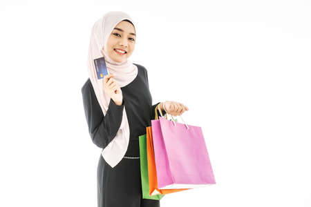 Portrait of beautiful asian muslim woman in a black hijab smiling cheerful with shopping bag and credit card  isolated over white background 免版税图像