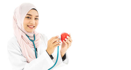 Portrait of beautiful young Muslim woman doctor shows a red heart  and wearing a stethoscope concept for Islam people working in heart medical hospital health care isolated on white background Stock Photo