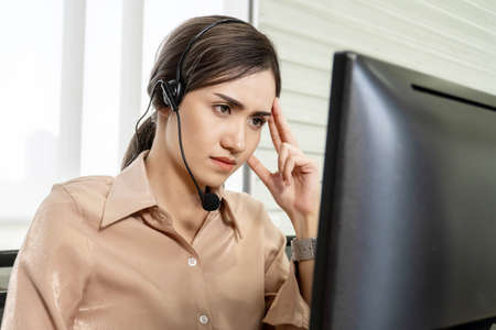Call center, Service desk consultant talking on hands-free phone,Young woman operator from call center thinking and looking computer expressing doubt and wonder