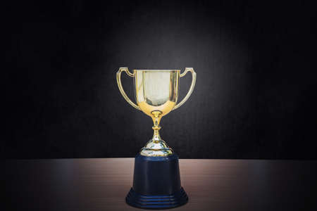 Golden trophy placed on top of old wooden table in front of dark background copy space ready for your design win concept. Standard-Bild