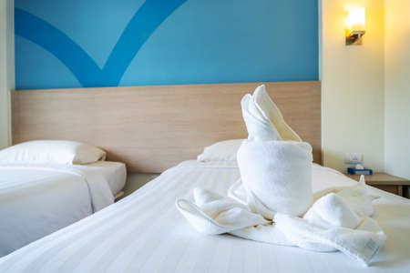 White towel on white bed decoration in bedroom interior of luxury boutique hotel