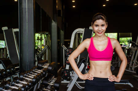 Portrait of fit young asian woman in sportswear posing standing in gym with her hands on hips. Sexy and sensual brunette woman with perfect body posing in studio with copyspace.