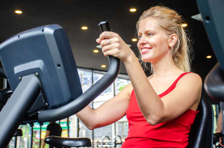 Portrait of young woman exercising using stationary bike in gym, Fitness class doing sport biking in the gym for health.