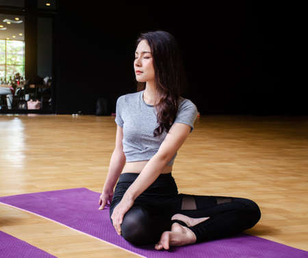 Young sporty woman attractive people practicing yoga lesson with basic pose with instructor, working out indoor, studio. Wellbeing,sports and healthcare concept