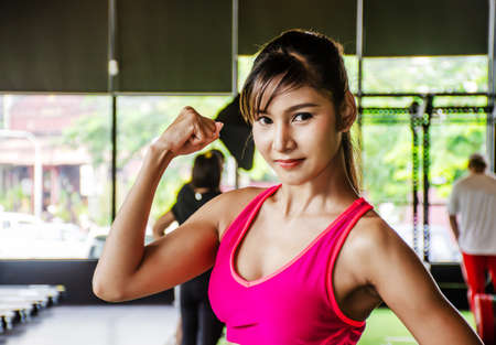 Young strong sexy woman showing her muscles on the arm in the gym. 写真素材