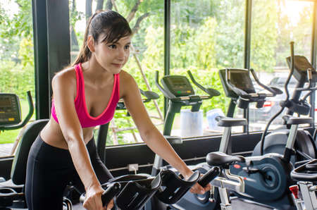 Young sporty woman cycling on bike machine in modern fitness gym,  Workout in Gym and fitness for health.