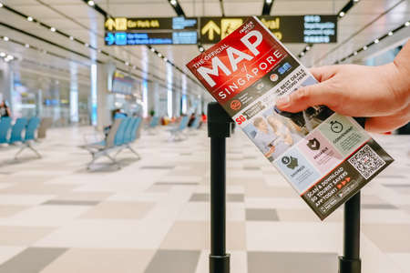 SINGAPORE - NOVEMBER  22, 2018: Passengers holding travel luggage with map at the airport