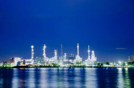 Night scene of oil refinery plant of Petrochemistry industry in twilight time and reflection in near river, gas and oil production processing in Bangkok, Thailand.