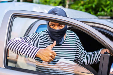 The male thief wears a black and white striped shirt and wears a black mask, smiling happily after stealing the car and getting a briefcase with money he wants.