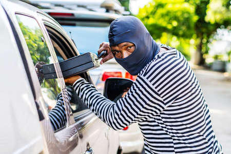 Transportation, crime and ownership concept -Young asian man thief stole a leather bag from a car whose windows