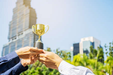 Businessman team holding award trophy for show their victory, Champion golden trophy for winner background, Success and achievement concept, Sport and cup award theme. Imagens