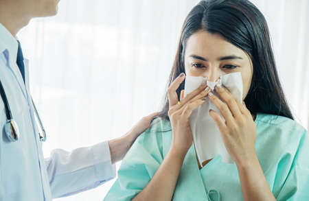 Primary care doctor making diagnosis to sick woman, unhappy patient using a tissue to sneeze and blowing her nose and get high fever from flu and cold, Patient care and healthcare.