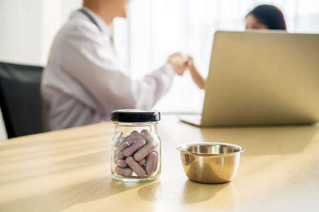 Bottle of pills and bowl doctor, male medicine doctor and patient working on background. Medicine doctor's working table. Healthcare and medical concept. Stock fotó
