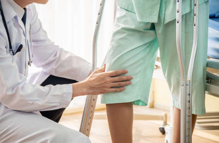 Asian male Doctor or Physiotherapist examining knee and helping patient to walk with crutches because injured legs of young patient women after accident and explain to her the diagnosis of problem.