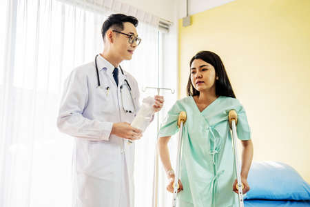 Front view of Asian male doctor helping female patient to walk out the hospital bed, Medicine and health care concept, selective focus point Stockfoto