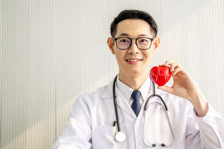 Doctor with stethoscope showing red heart at hospital office, Medical health care and doctor staff service concept.