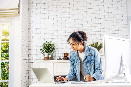 Young business smiling happy asian woman working on a laptop and writing down ideas in a paperwork at home, work from home concept