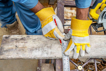 Construction worker wears protective leather gloves, with a pencil and the carpenter's square trace the cutting line on a wooden table. Construction industry, housework do it yourself. Standard-Bild
