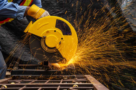 Industrial technician engineer in blue protective cloth wear safety mask, Man working with electric grinder tool on steel structure with   sparks flying in factory, selective focus Standard-Bild