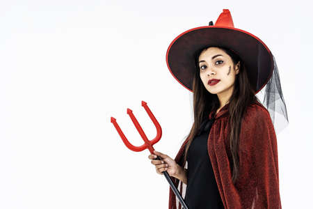 Halloween Party girl. Happy Halloween Witch with bright make-up and long hair holding weapon . Isolated on white background