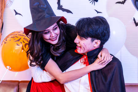 Halloween loving couple vampire in cloak and witch girl looking at each other, view of faces and hug together, Halloween or horror theme