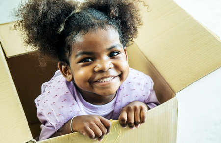 Happy cute active little african american kids girl play riding in cardboard boxes feel excited to move in new house, playful overjoyed black sister have fun Standard-Bild