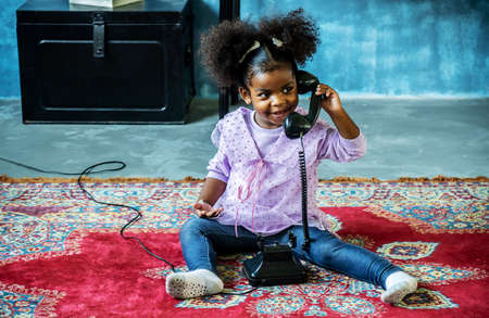 Cute little african american girl playing with vintage old dial phone on the carpet, Bonding time, educational playtime. Standard-Bild